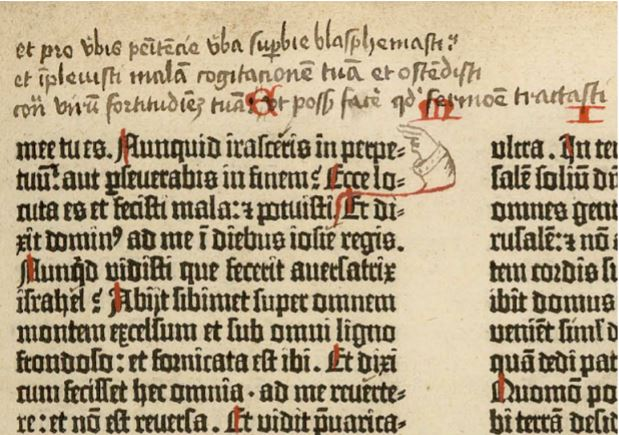 Close of up Gutenberg Bible with marginalia. The commentator drew a hand pointing from the text to his commentary.